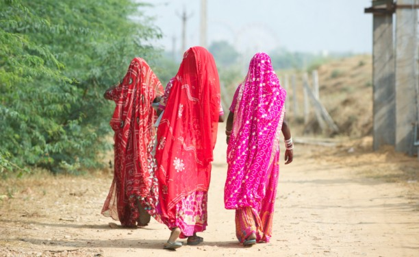 Indian women in clourful pink and red sari's walking away from camera